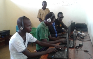 Stephen Odong (in white) practices on a laptop together with his colleagues at Oysters & Pearls -Uganda office