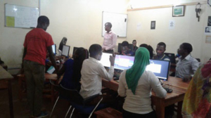 Students around computer monitors learning programming